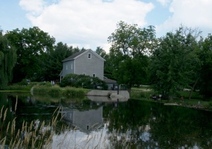 The mill reflected in the mill pond.   The park is a favorite place for young anglers.