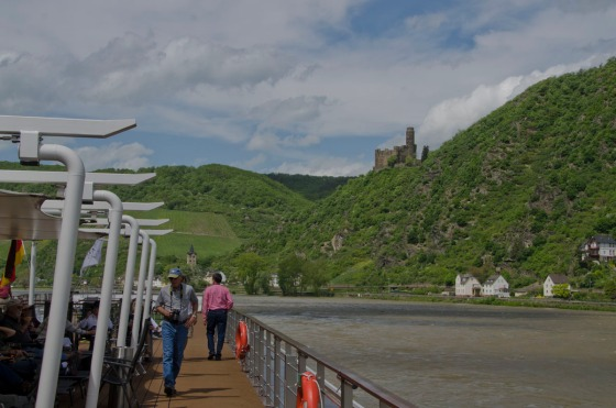 This picture shows passengers up on the sun deck (in the shade and out of the wind, on the left side) as we cruised down the Rhine looking at castles,like the one on the right.