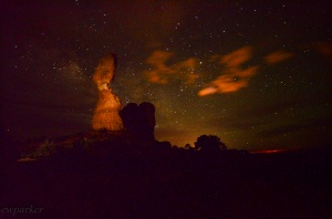 The orange glow in this shot is the light from Moab reflected off the clouds.  The rock is lit by flashlight painting.