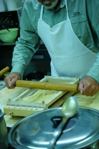 The chitarra in action - using a rolling pin the sheet of pasta is pressed through the wires, and long strands of noodles emerge.