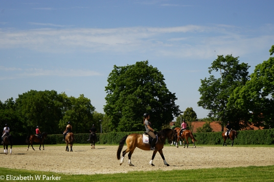 Riders practicing for the Olympic trial judging going on elsewhere at the stables.