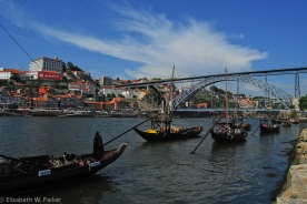 The port boats in the Douro River in front of the caves. The Dom Luis I Bridge is in the background.